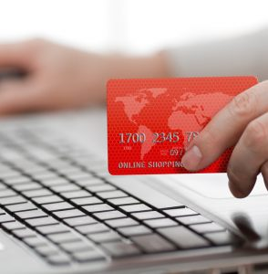 Man holding credit card in hand and entering security code using