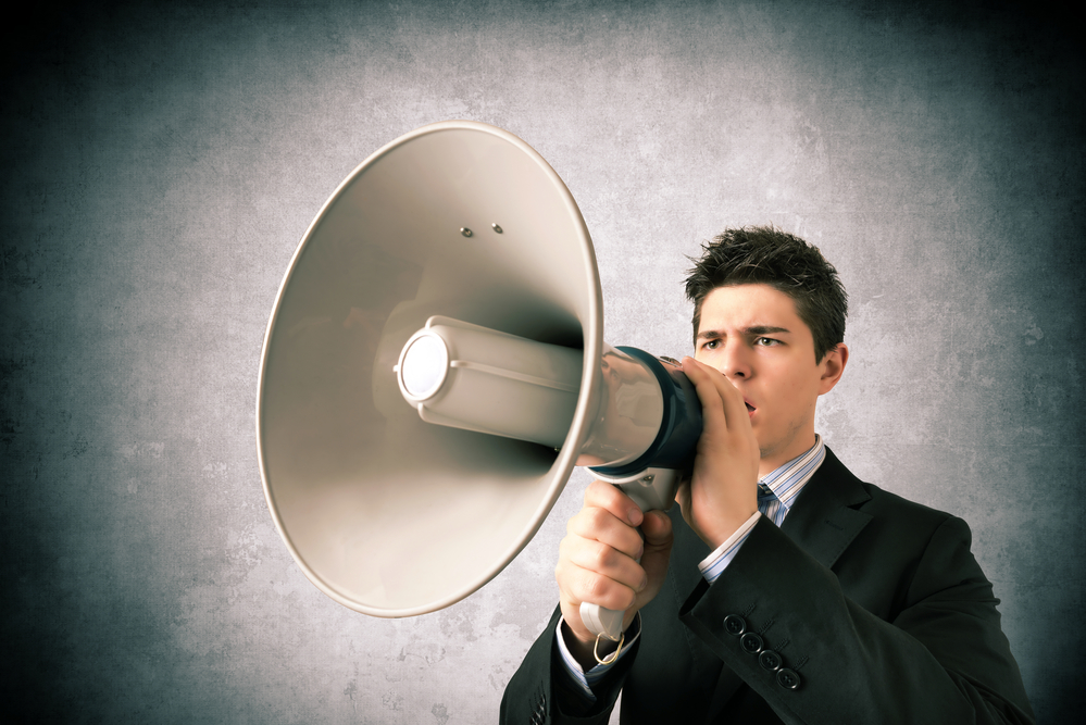Young business man speaking with a megaphone